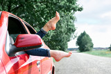 young woman driver resting in a red car, put her feet on the car window, happy travel concept - 220764556