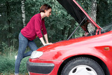 a young girl stands at a broken car and looks at the engine, does not understand how to repair - 220764738