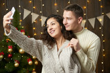 Happy couple taking selfie and having fun in christmas decoration. Dark wooden interior with lights. Romantic evening and love concept. New year holiday. - 220764764