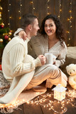 Happy couple drinking tea and talking in christmas decoration, sitting on floor in dark wooden interior with lights. Romantic evening and love concept. New year holiday. - 220764944
