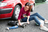 a young girl sits near a broken car and makes repairs to the electric generator, next to her there are bad parts, tools and first aid kit - 220764993