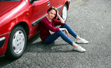 young girl sitting on the road by the red car - 220765186