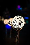 Night view of bright vintage lamp lantern with decoration. Selective focus with soft bokeh. - 220779998