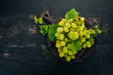 Fresh green grapes with leaves of grapes. Top view. On a black wooden background. Free space for text.