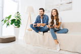 laughing couple playing video game by joysticks on sofa at home - 220786932