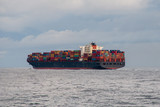 Container ship underway in the North Atlantic, well loaded. Calm seas and cloudy overcast sky.  - 220789116