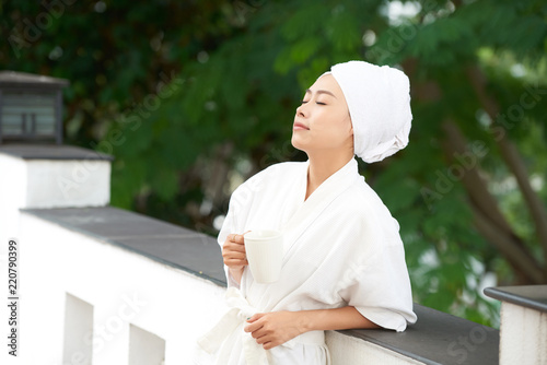 Sticker Beautiful Asian woman in white bathrobe and towel after shower standing with cup of coffee on terrace enjoying morning