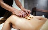 Masseur massaging masseuse at wellness resort - 220791127