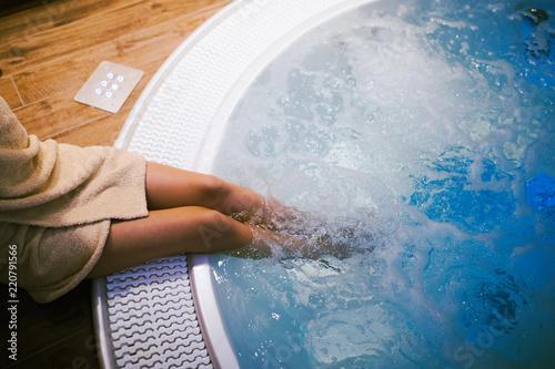 Leinwanddruck Bild Woman entering jacuzzi in spa resost