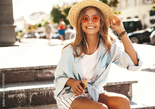 Leinwanddruck Bild Portrait of beautiful cute smiling blond teenager model in summer hipster clothes sitting on stairs on the street background and listening music on her mobile phone