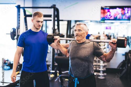 Older man assisting senior man at the gym. - 220795131