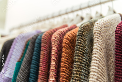 Nice warm colorful sweaters hang on hangers inside of a shopping mall. Beautiful  clothes for 4df0b53ed