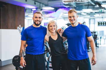 Three happy young people standing at the gym.