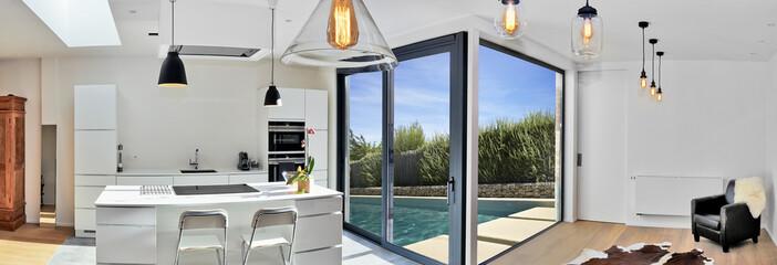 Modern kitchen from loft with view on a lush garden © pbombaert
