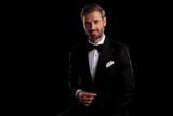 seated elegant man in tuxedo holding his button - 220808343