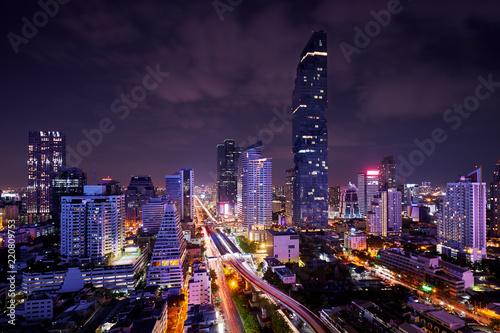 Leinwanddruck Bild night of urban cityscape in metropolis and light of sky train