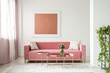 Pillows on pink sofa in white apartment interior with painting and flowers on copper table. Real photo