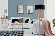 Leinwanddruck Bild - Lamp next to white couch with pink blanket in blue living room interior with posters. Real photo