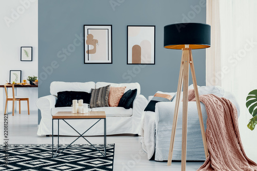 Lamp next to white couch with pink blanket in blue living room interior with posters. Real photo