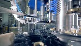 Factory equipment placing caps on bottles, close up. Automated industrial equipment. - 220816171