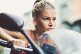 Young blonde women ride a motorcycle.  Portrait.  Close up. - 220816768