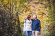 A portrait of a senior couple walking in an autumn nature. Copy space.