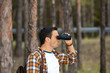 side view of tourist with backpack looking through binoculars in forest