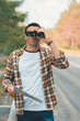 portrait of tourist with map and binoculars standing on road