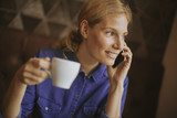 Pretty young woman with mobile phone in the cafe - 220829716