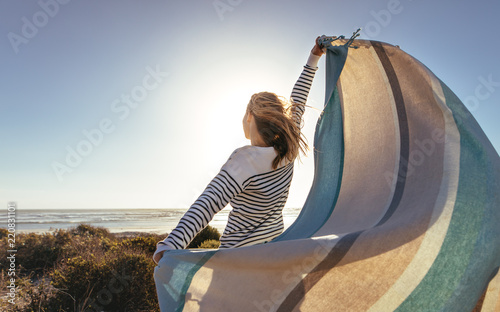 Leinwanddruck Bild Woman standing near the sea holding a drape
