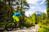 Tourist cycling in Cortina d'Ampezzo, stunning rocky mountains on the background. Man riding MTB enduro flow trail. South Tyrol province of Italy, Dolomites. - 220832347