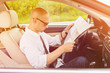 Man traveler in car looking at a paper map. Guy searching for place to go on a map. Closeup, vibrant warm colored image, no retouch, natural lighting.