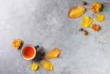 Cup of hot tea decorated by yellow autumn leaves, aster flowers and acorns over grey texture background. Flat lay, space. Seasonal background. - 220836540