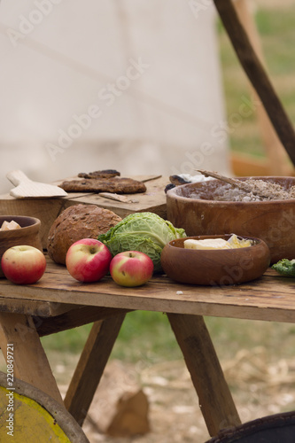 Medieval food preparation including bread, butter, cheese, fruit in