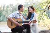 young couple sitting on a log by the river and playing guitar, summer nature, bright sunlight, shadows and green leaves, romantic feelings - 220852592