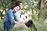 young couple sitting in the forest and playing guitar, summer nature, bright sunlight, shadows and green leaves, romantic feelings - 220852739