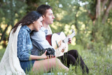 young couple sitting in the forest and playing guitar, summer nature, bright sunlight, shadows and green leaves, romantic feelings - 220852786