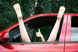 young woman driver resting in a red car, put her feet on the car window and gesturing, happy travel concept - 220852924