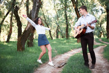 young couple walking in the forest and playing guitar, summer nature, bright sunlight, shadows and green leaves, romantic feelings - 220852982
