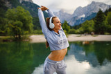 Young sports woman stretching arms at dock on the lake in the mountains - 220862301
