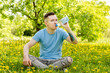 Leinwandbild Motiv Young guy dressed in a blue t-shirt, drinks water from a bottle, sits on a green grass and yellow dandelion background.