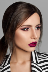 Studio portrait of attractive brunette model with perfect skin and professional evening make-up wearing sexy black and white striped jacket ove bra over grey background. © Вячеслав Косько