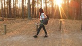 Gorgeous girl dressed in t-shirt and pants with backpack holds thermos and yoga mat while walking in beautiful autumn forest. - 220876906