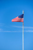 American flag on top white flagpole, flying in the breeze, blue sky background, wispy white cloud, stars and stripes, red, white, and blue - 220891102