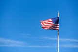 American flag on top white flagpole, flying in the breeze, blue sky background, wispy white cloud, stars and stripes, red, white, and blue - 220891148