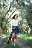 young woman walking in the forest and playing guitar, summer nature, bright sunlight, shadows and green leaves, romantic feelings - 220908508