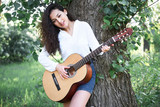 young woman walking in the forest and playing guitar, summer nature, bright sunlight, shadows and green leaves, romantic feelings - 220908532