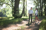 young couple walking in the forest, summer nature, bright sunlight, shadows and green leaves, romantic feelings - 220908548