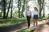 young couple walking in the forest, summer nature, bright sunlight, shadows and green leaves, romantic feelings - 220908595