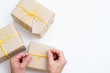 holiday congratulation gifts. handcrafted packages with presents inside. hands making a bow with yellow twine. three craft boxes on white background.